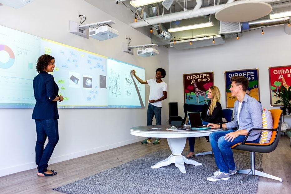 réunion de brainstorming dans une salle de créativité hoylu avec un mur digital